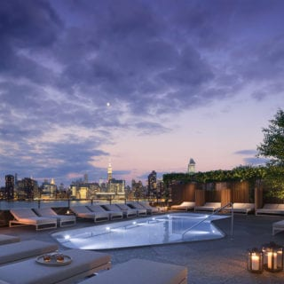 photo of 2 blue slip pool at night looking over manhattan